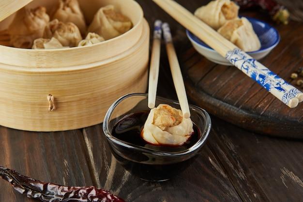 Shumai shaomai chinese gestoomde schotel met vleesknoedel in bamboestoomdoos. eetstokjes en dimsum.