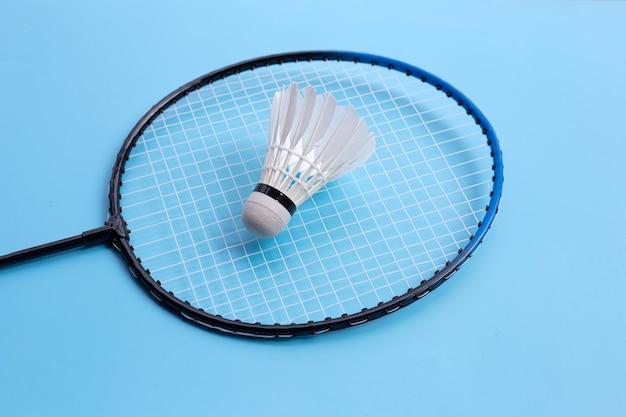 Shuttle en badmintonracket op blauwe achtergrond. kopieer ruimte