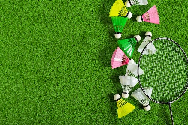 Shuttle en badmintonracket op groen gras