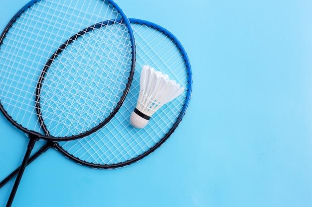 Shuttle en badmintonrackets op blauwe achtergrond. kopieer ruimte