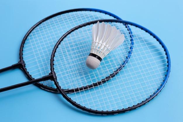 Shuttle en badmintonrackets op blauwe achtergrond.