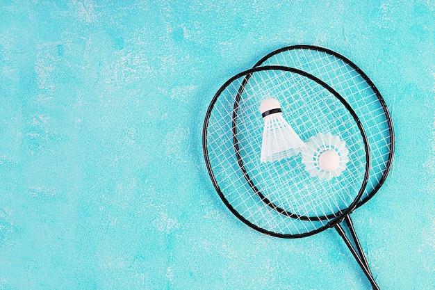 Shuttle en badmintonrackets op een blauwe achtergrond. bovenaanzicht