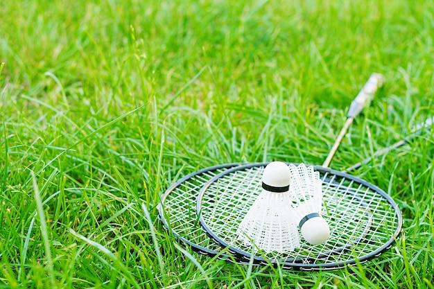 Shuttle en badmintonrackets op een groen gazon