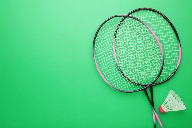 Shuttle en badmintonrackets op groen.