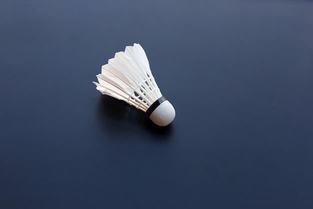 Shuttle of badmintonbal op donkere muur.