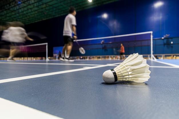 Shuttle pik badminton in het blauwe hof met het spelen van badminton.