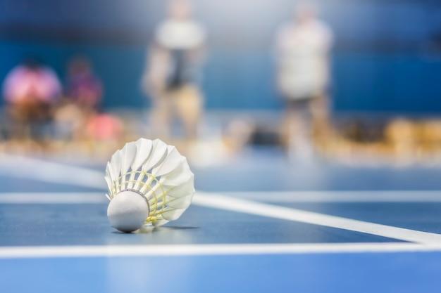 Shuttle pik badminton in het blauwe veld met badminton spelen