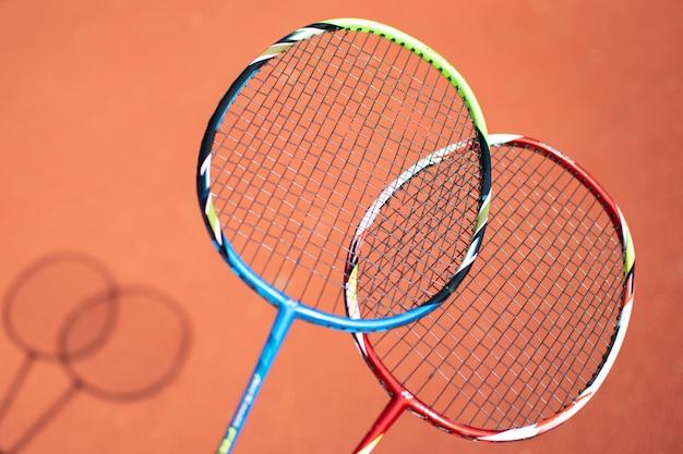 Shuttles en badmintonracket op oranje achtergrond.