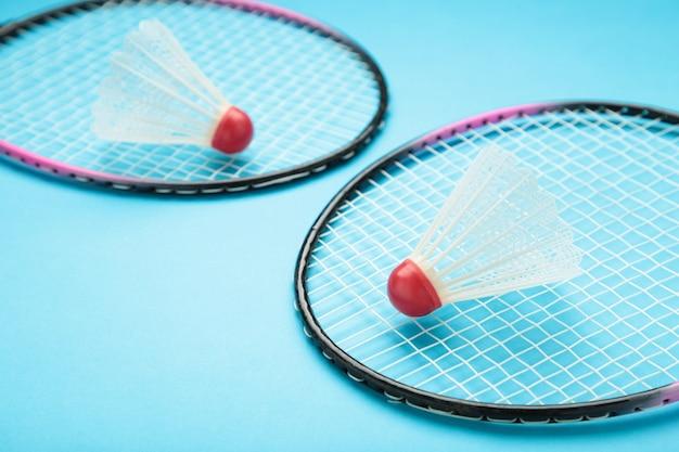 Shuttles en badmintonrackets op blauw.