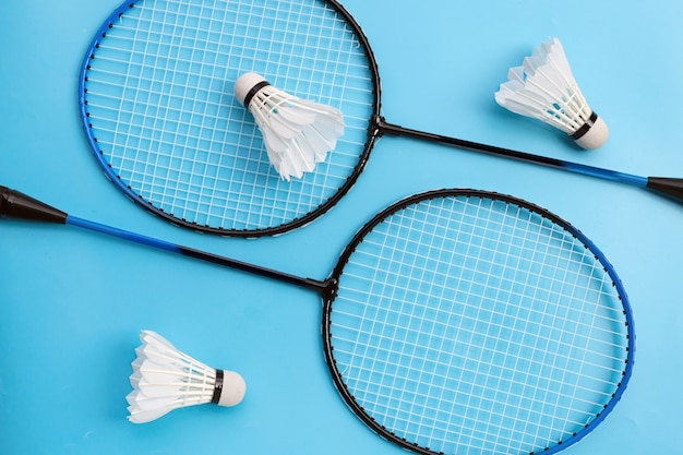 Shuttles en badmintonrackets op blauwe achtergrond. bovenaanzicht