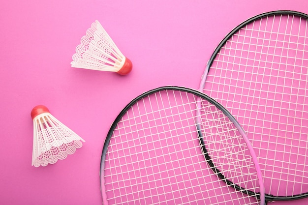 Shuttles en badmintonrackets op roze.