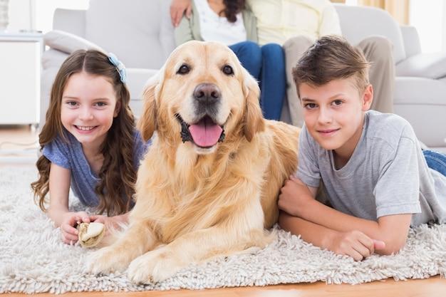 Siblings die met hond liggen terwijl ouders die op bank ontspannen