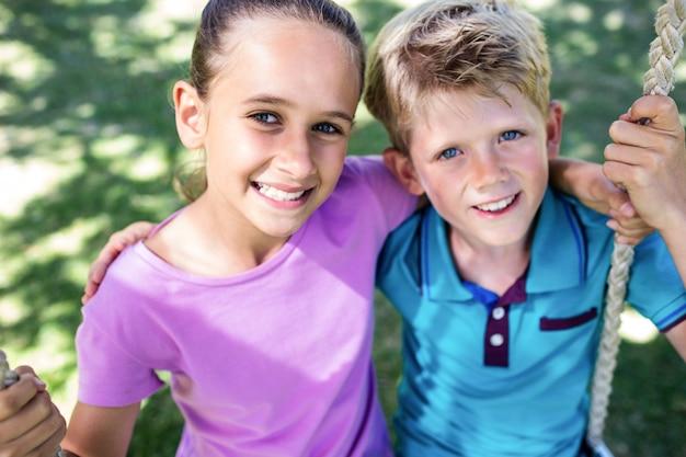 Siblings die op een schommeling in het park zitten