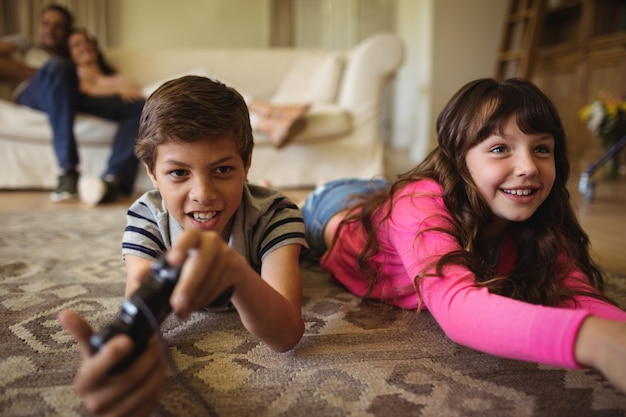 Siblings die op tapijt liggen en videospelletje spelen