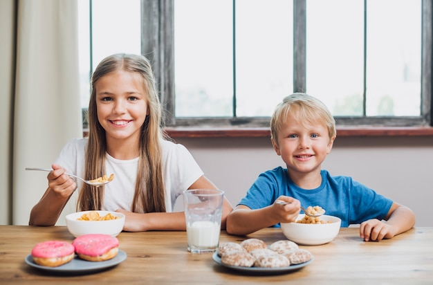 Siblings die samen in de keuken eten