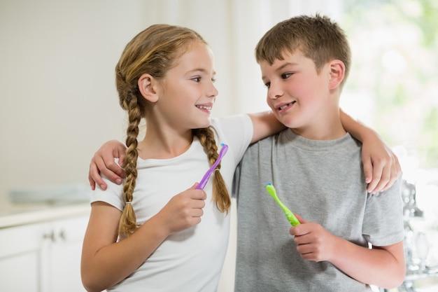 Siblings die tanden in badkamers borstelen