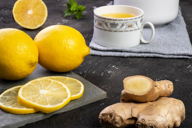 Siciliaanse citroenthee met gember en muntblaadjes op leisteen.