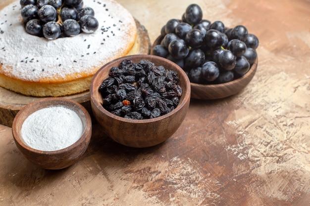 Side close-up bekijken een cake een smakelijke cake op het bord kommen van druiven suiker rozijnen