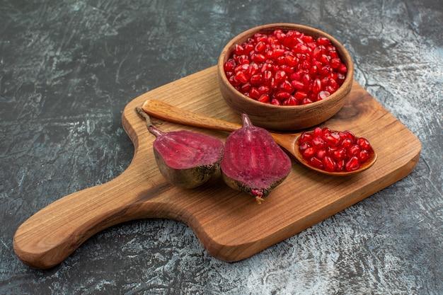 Side close-up weergave groenten de snijplank met de smakelijke granaatappel zaden lepel bieten