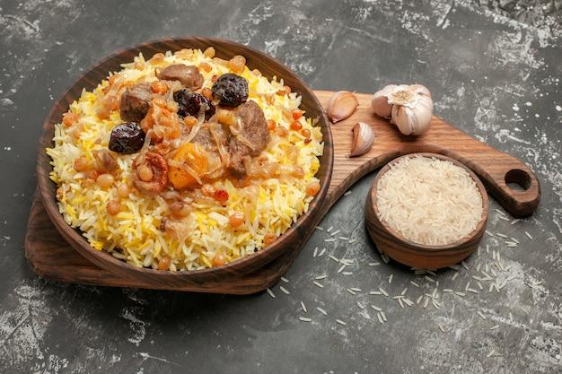 Side close-up weergave pilaf knoflook kom rijst een smakelijke pilaf op de houten keuken bord