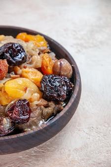 Side close-up weergave pilaf pilaf van rijst gedroogd fruit kastanjes op tafel