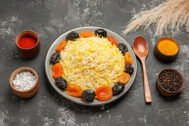 Side close-up weergave rijst kleurrijke kruiden lepel plaat rijst met gedroogde vruchten