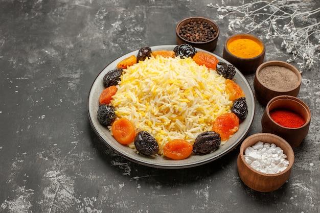 Side close-up weergave rijst plaat van rijst met gedroogde vruchten kommen van kleurrijke kruiden boomtakken