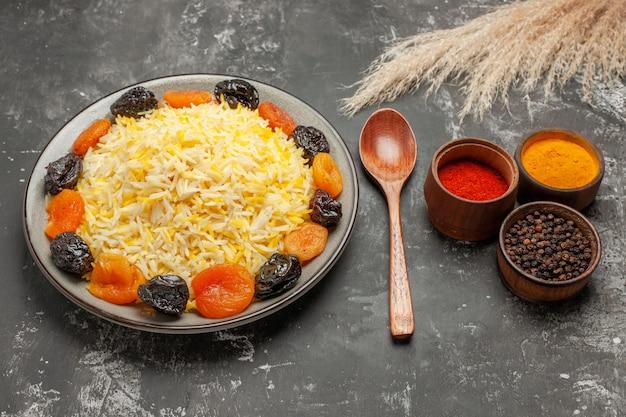 Side close-up weergave rijst plaat van rijst met gedroogde vruchten kommen van kleurrijke kruiden lepel