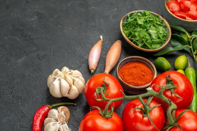 Side close-up weergave tomaten knoflook ui hete pepers tomaten kruiden kruiden op de zwarte tafel