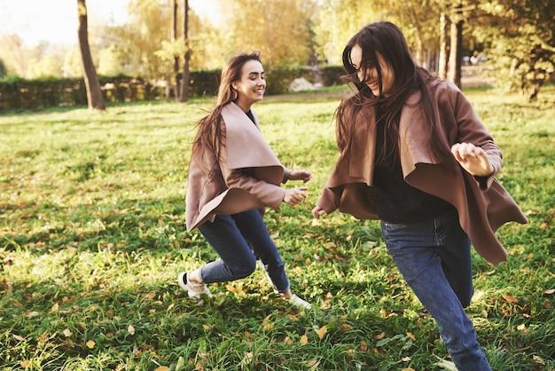 Side profiel van jonge lachende brunette tweeling meisjes met plezier, rennen en elkaar achtervolgen in herfst zonnig park op onscherpe achtergrond.
