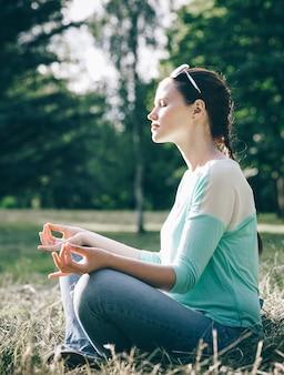 Side view.beautiful vrouw mediteren in de lotuspositie buitenshuis. het concept van rust en meditatie