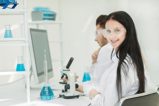 Side view.female wetenschapper zittend aan een lab tafel. wetenschap en gezondheid