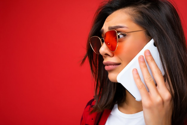 Sideprofile close-up foto van aantrekkelijke trieste jonge donkerbruine vrouw, gekleed in een stijlvol rood shirt wit