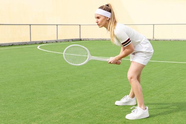 Sideway tennisvrouw met racket