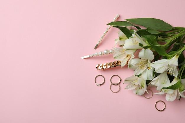 Sieraden en bloemen op roze achtergrond, ruimte voor tekst