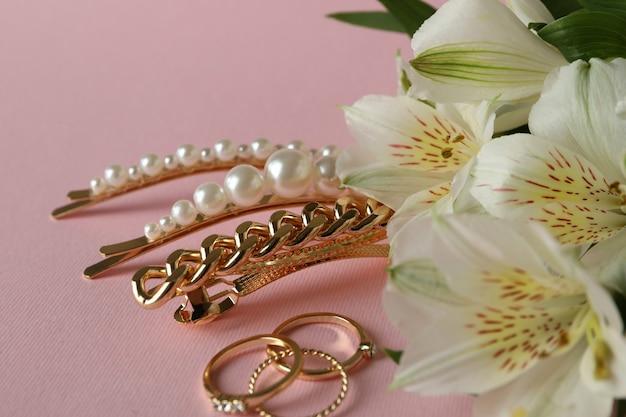 Sieraden en bloemen op roze, close-up