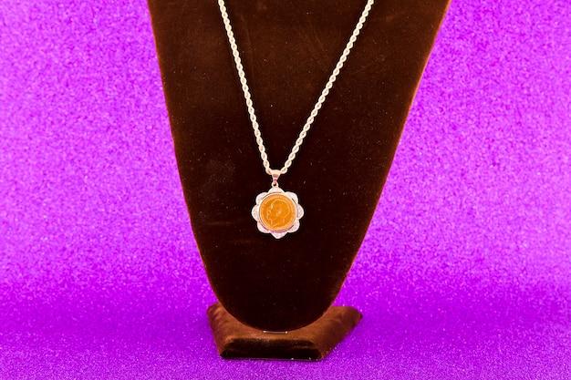 Sieraden gouden nek kettingen geïsoleerd op paarse achtergrond
