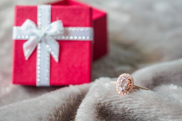 Sieraden roze diamanten ring met rode geschenkdoos achtergrond