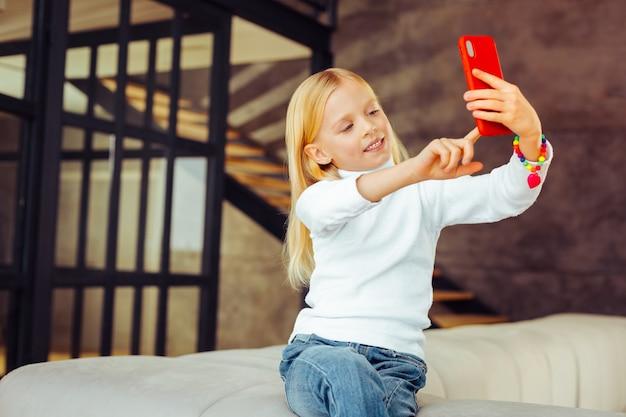 Sieraden voor kinderen. attente kleuter die haar glimlach demonstreert terwijl ze selfie doet