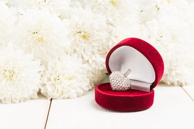 Sieradenhart in geschenkdoos, teken van liefde voor valentijnsdag met witte bloemen