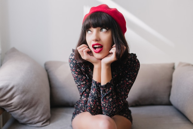 Sierlijk brunette meisje in trendy franse baret en vintage jurk herinnerde zich iets belangrijks. portret van charmante jonge vrouw, gekleed in kort kapsel, zittend op de bank met grappige gezichtsuitdrukking