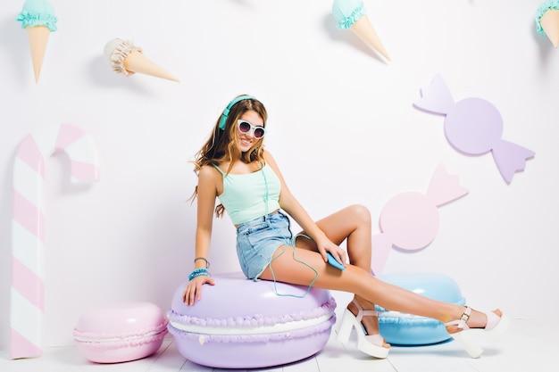 Sierlijk lachend meisje met hakken sandalen zittend op paarse makaron stoel en muziek luisteren. portret van mooie jonge vrouw in zonnebril met innemende glimlach genieten van lied.