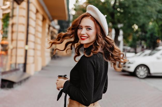 Sierlijk langharig gembermeisje dat over schouder kijkt. mooie vrouw lachen in baret genieten van wandeling.
