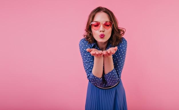 Sierlijk meisje in blauwe jurk poseren met gesloten ogen en luchtkus verzenden. jonge vrouw met kort golvend haar geïsoleerd op roze muur met kussende gezichtsuitdrukking.