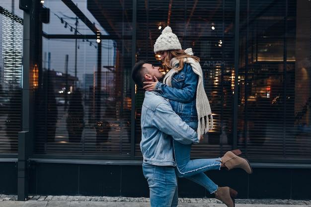 Sierlijk meisje in gebreide sjaal en hoge haklaarzen die pret hebben tijdens date. openluchtportret van europese kerel die zijn vriendin op stedelijke straat houdt.