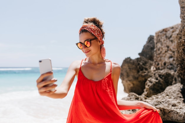 Sierlijk meisje in sparkle zonnebril selfie maken in weekend in zomerverblijf. buiten schot van zalige gebruinde dame die een foto van zichzelf neemt terwijl ze aan het chillen is op het strand van de oceaan.