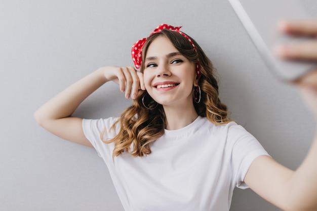 Sierlijk meisje in trendy oorbellen met smartphone voor selfie. binnen schot van vrij europese dame in witte kledij die thuis stelt.