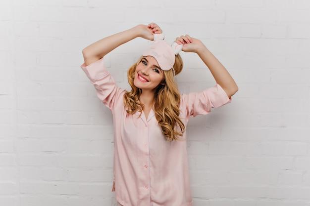 Sierlijk meisje met golvend haar poseren in roze zijden nachtkostuum. positieve jonge vrouw in oogmasker dansen in de ochtend.