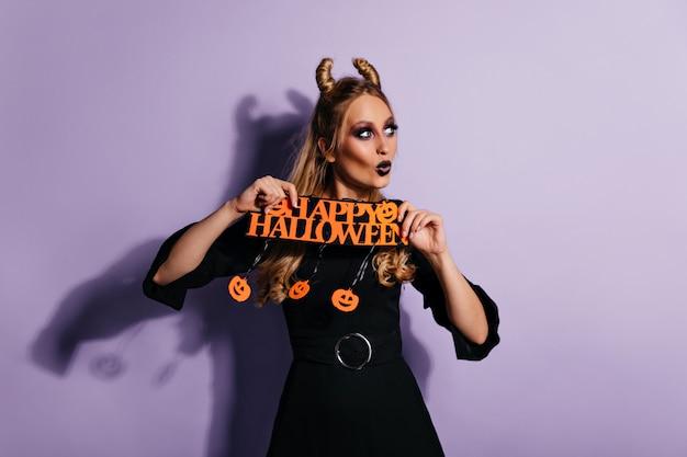 Sierlijk slank meisje met plezier op halloween. mooie vrouw in heksenkostuum poseren op violette muur.