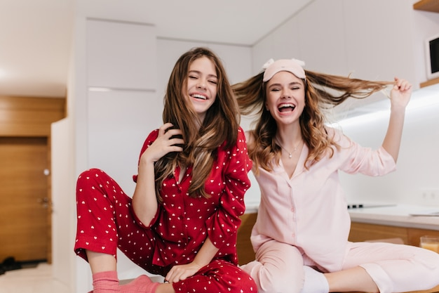 Sierlijk wit meisje met krullend kapsel genieten van goedemorgen met zus. binnenopname van geïnspireerde blanke vrouwelijke modellen in nachtkostuums die met hun haar spelen.